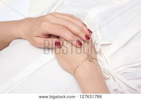 Woman's hands elegantly resting on her belly while relaxing