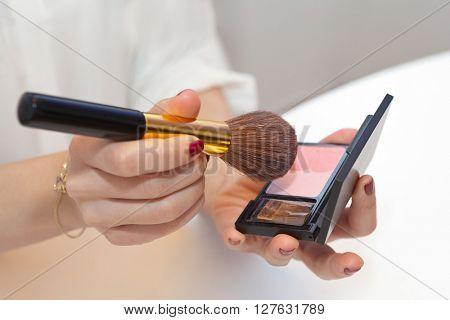 Professional make up brush in hand on pink blush