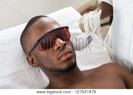 Close-up Of Therapist Giving Laser Epilation Treatment On Young African Man