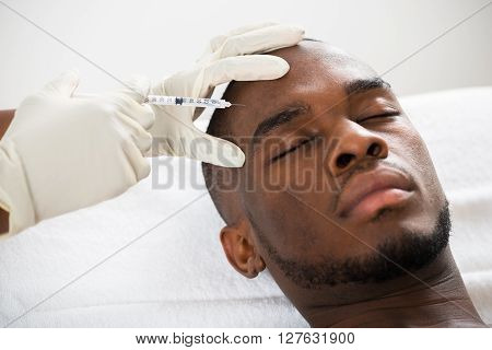 Person Hand Injecting Syringe On Young Man Face