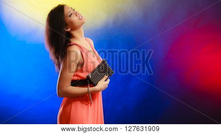 Fashion elegant evening outfit. Stylish woman fashionable mixed race girl orange party gown holding black leather handbag bag night club