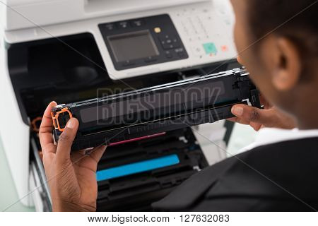 Businesswoman Fixing Cartridge In Office