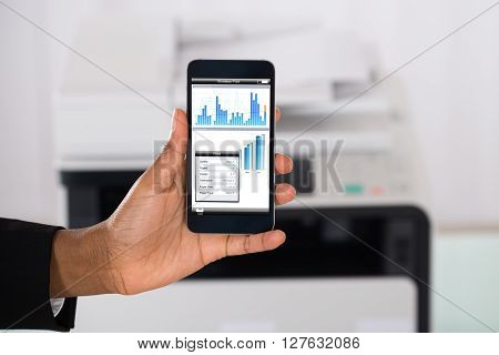 Businesswoman Using Smartphone For Printing Graph Paper