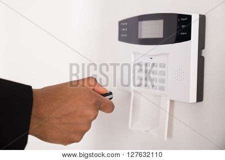 Businesswoman Using Remote Control For Operating Security System