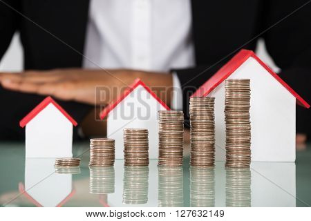Businesswoman With House Model And Stacked Coins On Desk
