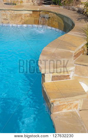 Luxurious swimming pool in backyard of a residential home.