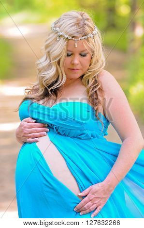 Stunning maternity portrait of beautiful blonde in a blue strapless dress outdoors.