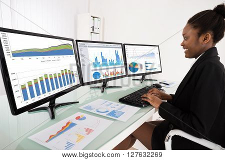 Businesswoman Analyzing Graph On Multiple Computer