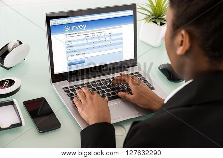 Close-up Of A Businesswoman Filling Online Survey Form