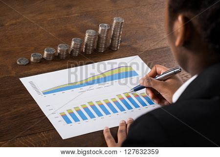 Businesswoman Analyzing Financial Graph With Coins On Desk