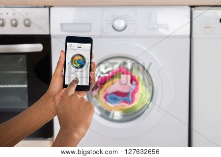 Woman's Hand Operating Washing Machine With Mobile Phone