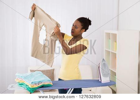 Woman Looking At Iron Burned Cloth