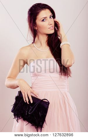 Beauty fashion and elegant people concept - young brunette slim woman in bright strapless dress holds black clutch bag