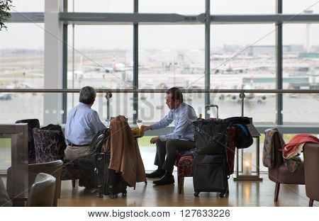 LONDON, UK - APRIL 7, 2016: Businessmen having a drink in departure launch of Heathrow airport