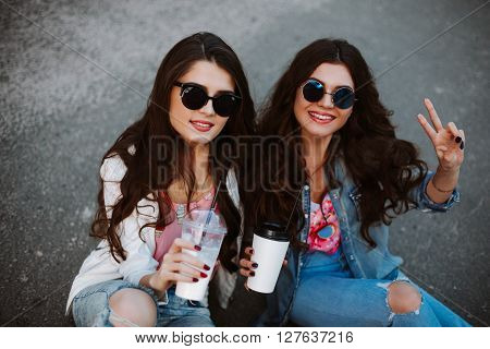 Best friend having fun on the roof, freaking out together, wearing bright floral shirts, denim jackets and mirrored glasses show a sign of peace, enjoy vacation