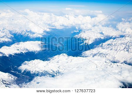 Snow covered mountains and rocky peaks in the French Alps, over blue sky. View from airplane