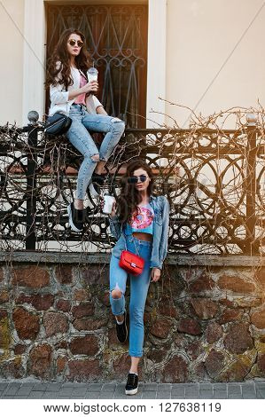 Outdoor fashion lifestyle portrait of two young beautiful women, dressed in denim outfit, mirrored sunglasses, enjoy a stroll, drink coffee, bright stylish clothes, accessories.