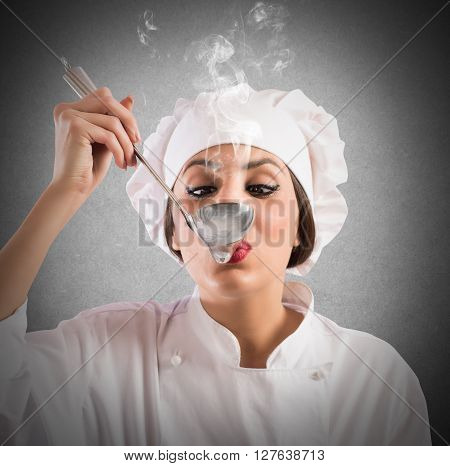 Woman taster chef tastes a steaming ladle