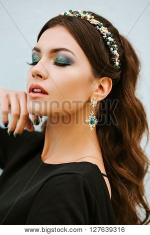 Portrait of fashionable girl brunette with a gorgeous bright makeup. The eyes are closed. Stylish expensive jewelry, a headband, a Hoop with precious stones, diamond earrings