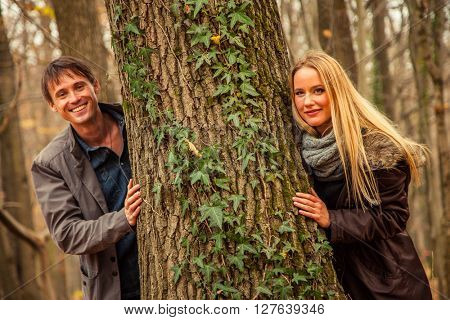 Young couple stand next to tree one a cross the other.
