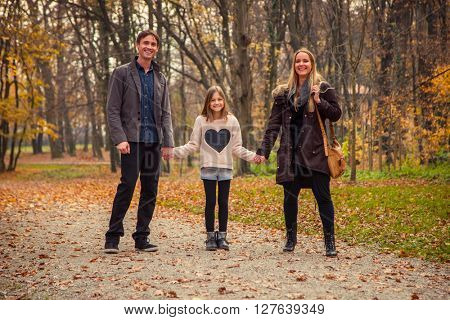Family of three walk in a park on an autumn day.