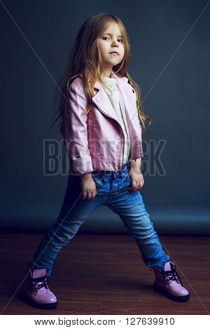 beautiful child wearing jeans and leather jacket in the studio