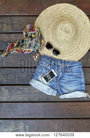 Summer music festival outfit on the wooden background - top view