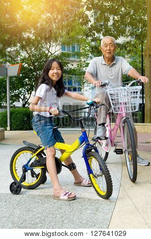 Little Asian girl and grandfather riding on bicycle with great fun