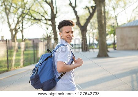 Young educated boy with packpack walk on college campus photographed in New York City in April 2016.