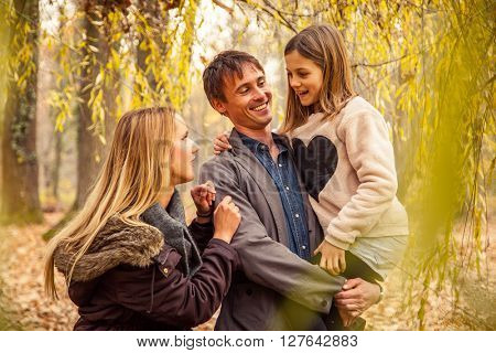Father holds daughter with mother next to them under tree canopy.