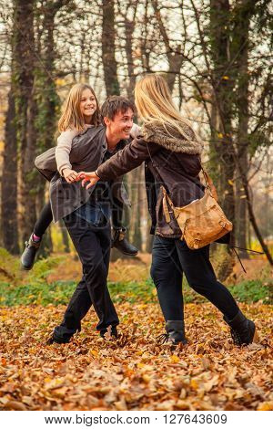 Daughter rides father on piggyback with mother next to them in park on an autumn day.