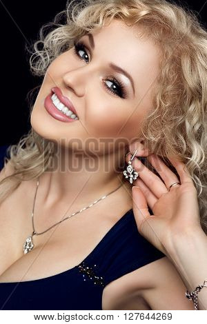 Studio portrait of gorgeous blonde woman smiling, darling necklace on her neck, earrings with precious stones touched by the hand. Makeup gold, black hands, looks into the camera. Black background