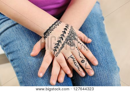 Henna ornaments on girl's hand closeup