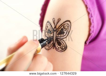 Image of butterfly painted with henna on girl's arm closeup
