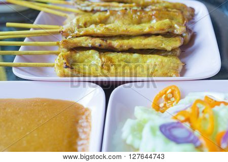 the pork satay with the dipping sauce with vegetable