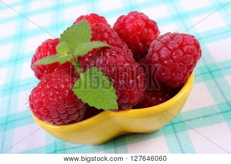 Fresh raspberries and leaf of lemon balm on checkered tablecloth concept of healthy food and dessert
