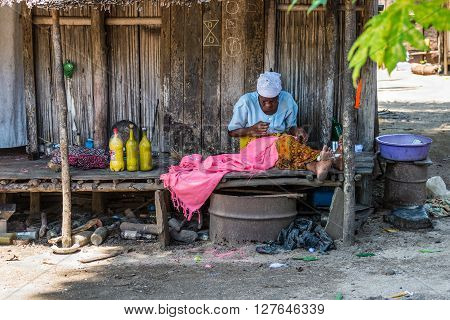 Ampasipohy Nosy Be Madagascar - December 19 2015: Malagasy old woman sits near wooden house in the rural village of the Ampasipohy Nosy Be Island Madagascar.