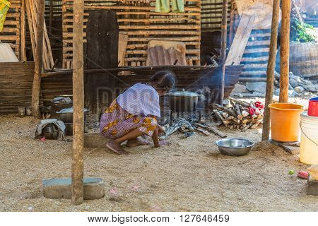 Ampasipohy Nosy Be Madagascar - December 19 2015: An outdoor kithchen with and old woman cooking food in the rural village of the Ampasipohy Nosy Be Island Madagascar.