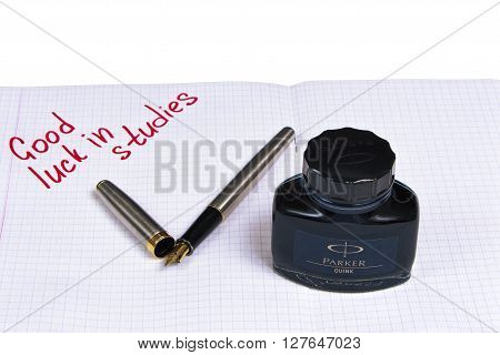 Silver with gold nib fountain pen, and a tube of blue-black ink on the background notebook with a signature.