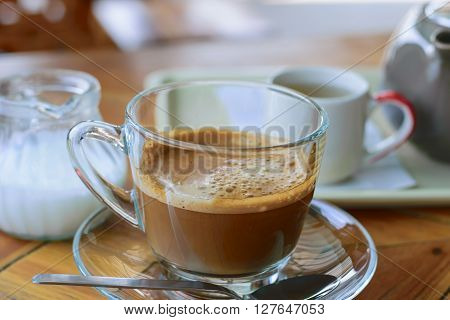 Morning cup of hot coffee with cream on table
