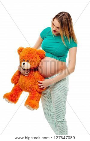 Pregnant woman holding teddy bear on her belly, isolated on white background