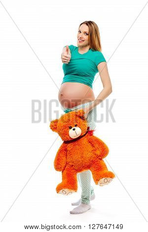 Beautiful pregnant blond woman in pajamas holding a toy bear and showing thumbs up all is well, super. White background
