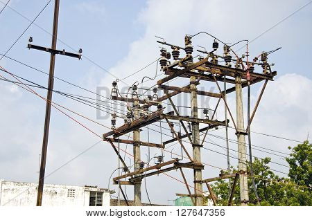 rusted electricity poles with many wires in urban area India