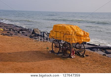 India Puducherry trolley with orange tied material by the sea