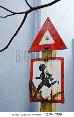 red black and white road sign in city street near school with a running child India