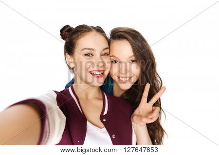 people, friends, teens and friendship concept - happy smiling pretty teenage girls taking selfie and showing peace sign