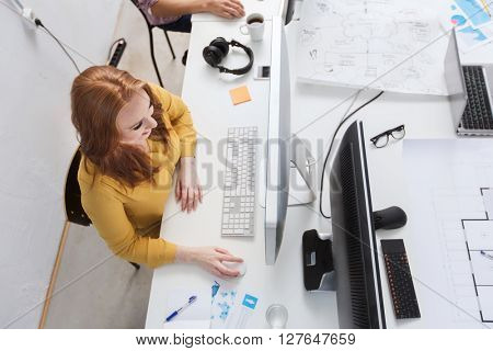 business, education, technology, people and internet concept - smiling creative woman or student with computer at office