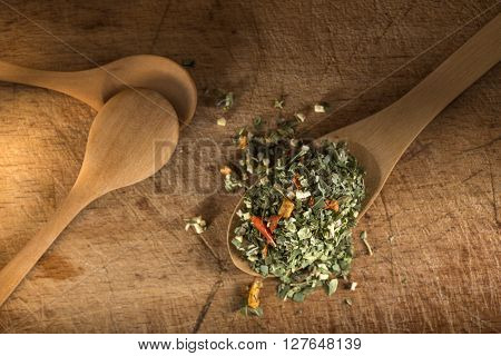 Wooden spoon with Italian seasoning - dried oregano with thyme basil and vegetables