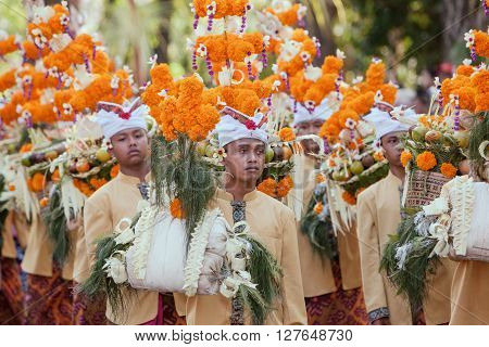 DENPASAR BALI ISLAND INDONESIA - JUNE 13 2015: Group of beautiful young men in traditional Balinese people costumes carry religious offering for hindu ceremony on parade at art and culture festival