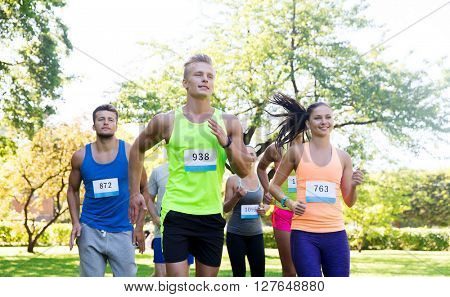 fitness, sport, race and healthy lifestyle concept - group of happy teenage friends or sportsmen running marathon with badge numbers outdoors
